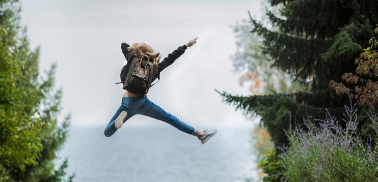 una ragazza con lo zaino che salra a gambe e braccia aperte a indicare l'importanza delle emozioni nel marketing