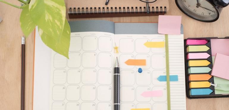 calendario da tavolo con post it penna e occhiali su una scrivania per decidere cosa pubblicare sui social media